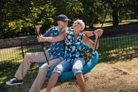 An older couple playing on a swing in a park.