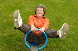 Aktive, fröhliche Seniorin auf einem Spielplatz-Spielgerät